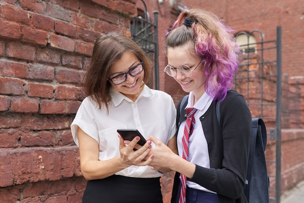 Adolescente étudiante en uniforme scolaire avec sac à dos marche parler avec enseignante