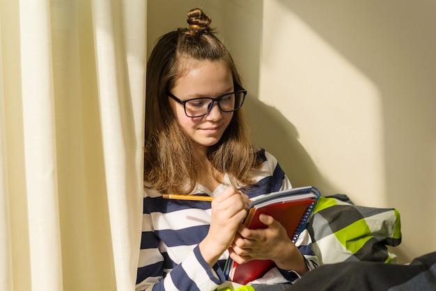 Une adolescente étudie à la maison