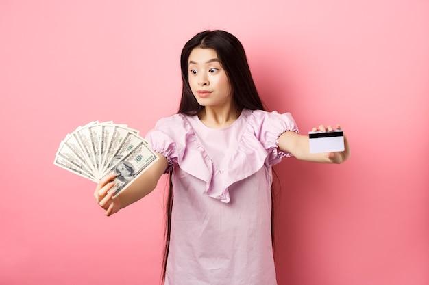 Adolescente excitée asiatique étendre les mains avec des billets d'un dollar et une carte de crédit en plastique, regarder l'argent avec étonnement, debout sur fond rose.
