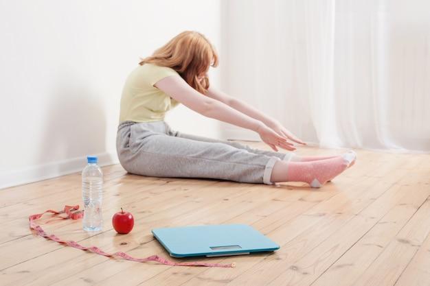 Adolescente, faire du sport à la maison, balances électroniques sur le sol