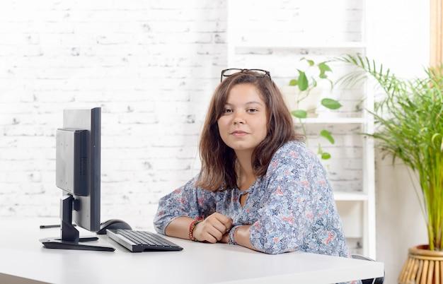 Une adolescente fait ses devoirs avec son ordinateur