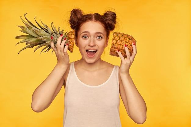 Adolescente, femme de cheveux roux à la recherche heureuse avec deux petits pains. portant une chemise blanche et tenant un ananas coupé à côté de son visage, mode de vie sain. regarder isolé sur mur jaune