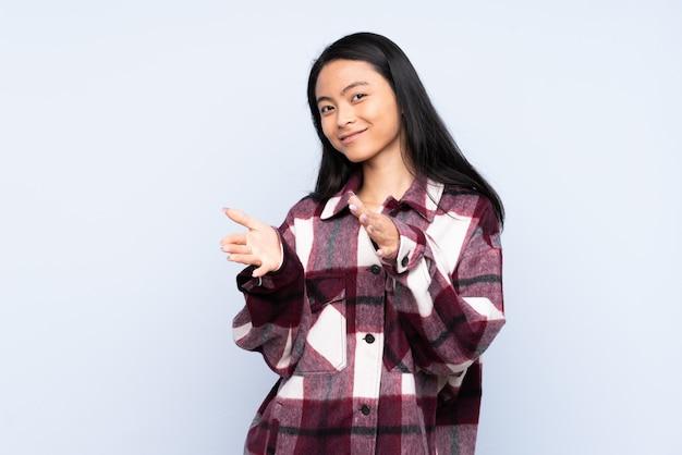 Adolescente femme chinoise sur mur bleu applaudissant après présentation lors d'une conférence