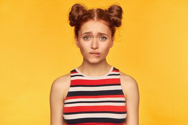 Adolescente, femme heureuse aux cheveux roux avec deux petits pains. porter un débardeur rayé et se mordre la lèvre, en attente, isolé sur un mur jaune