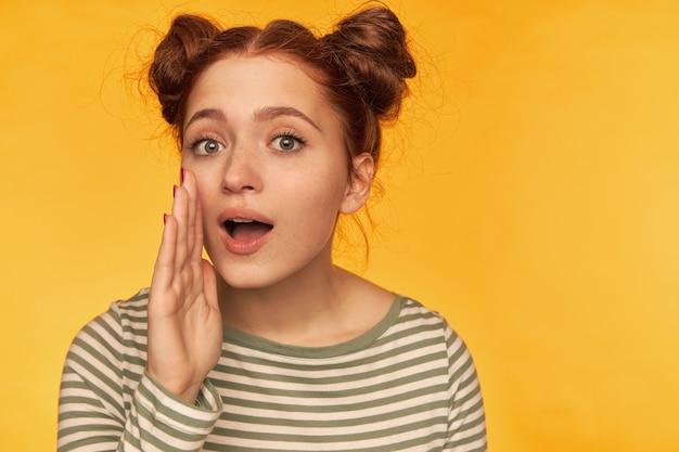 Adolescente, femme heureuse aux cheveux roux avec deux petits pains. vêtue d'un chemisier rayé et tenant la main près de sa bouche, murmure-toi. isolé sur mur jaune