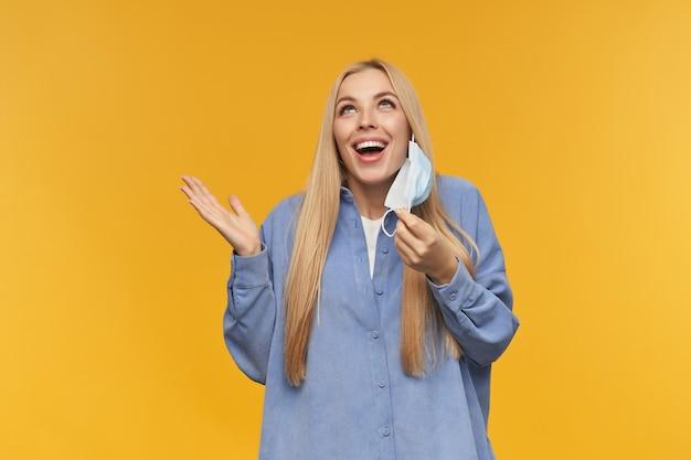 Adolescente, femme à la recherche heureuse aux cheveux longs blonds. enlevez son masque médical avec un large sourire. concept de personnes et d'émotion. watching up at copy space, isolé sur fond orange