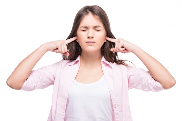 Une adolescente a fermé ses oreilles avec ses doigts.