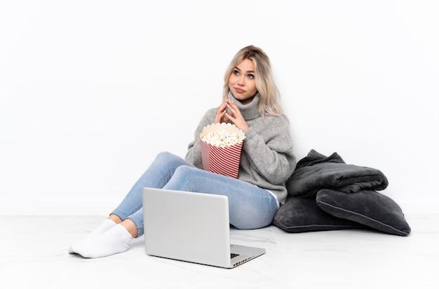 Adolescente fille blonde mangeant du pop-corn tout en regardant un film sur l'ordinateur portable quelque chose de complot
