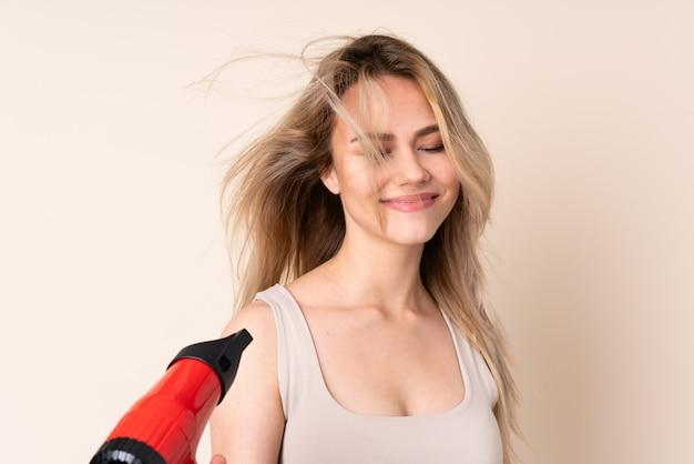 Adolescente fille blonde avec sèche-cheveux sur mur