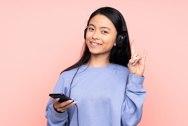 Adolescente fille chinoise isolée sur fond rose en écoutant de la musique avec un mobile faisant un geste rock