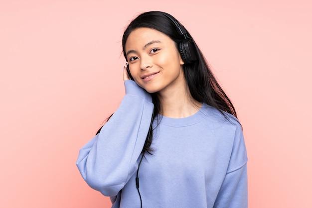 Adolescente fille chinoise isolée sur fond rose, écouter de la musique