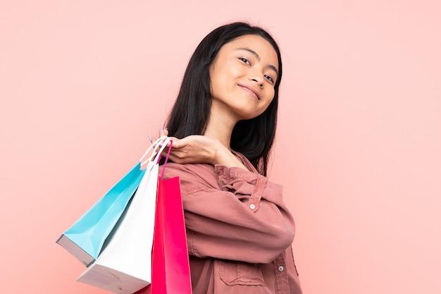 Adolescente fille chinoise isolée sur fond rose tenant des sacs à provisions et souriant
