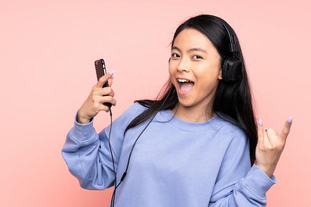 Adolescente fille chinoise sur mur rose écouter de la musique faisant un geste rock