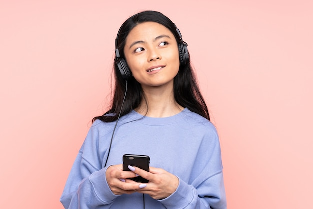 Adolescente fille chinoise sur mur rose écouter de la musique avec un mobile et penser