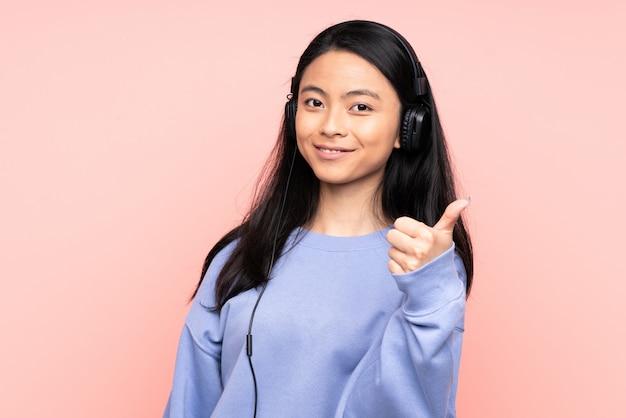 Adolescente fille chinoise sur mur rose écouter de la musique et avec le pouce vers le haut
