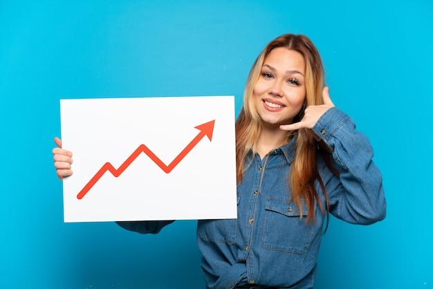 Adolescente sur fond bleu isolé tenant une pancarte avec un symbole de flèche de statistiques croissantes et faisant un geste téléphonique