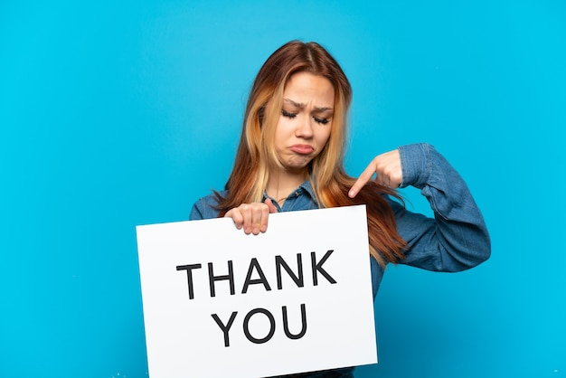 Adolescente sur fond bleu isolé tenant une pancarte avec texte merci et en le pointant
