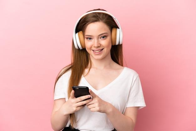 Adolescente sur fond rose isolé, écouter de la musique avec un mobile et à l'avant