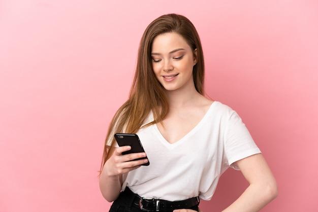 Adolescente sur fond rose isolé envoyant un message ou un e-mail avec le mobile