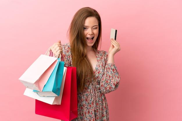 Adolescente sur fond rose isolé tenant des sacs à provisions et une carte de crédit