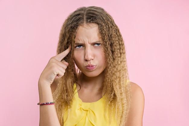 Adolescente fronçant les sourcils tout en regardant ailleurs avec un regard placide et pensif