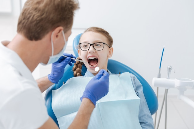 Adolescente géniale mignonne assise avec la bouche ouverte tout en visitant régulièrement son dentiste pour un examen général