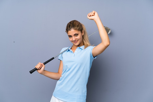 Adolescente golfeuse sur mur gris célébrant une victoire