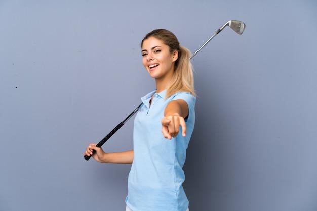 Une adolescente golfeuse sur un mur gris pointe le doigt vers vous avec une expression confiante