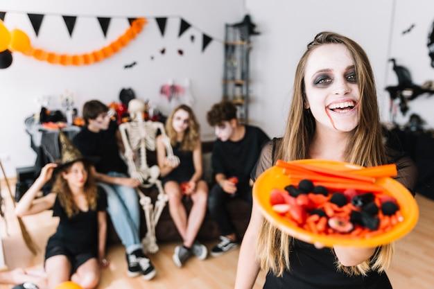 Adolescente avec halloween sinistre et assiette avec des bonbons