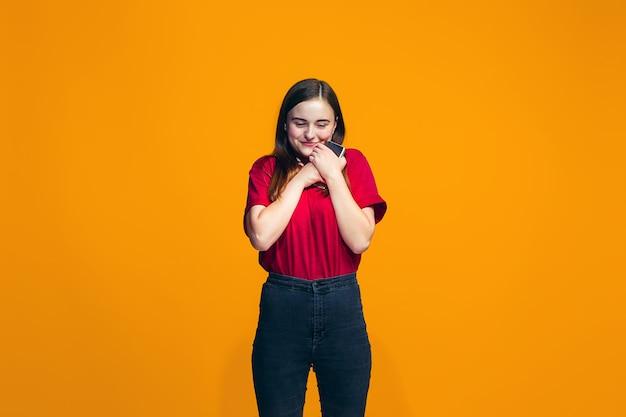 L'adolescente heureuse debout et souriant contre le mur orange