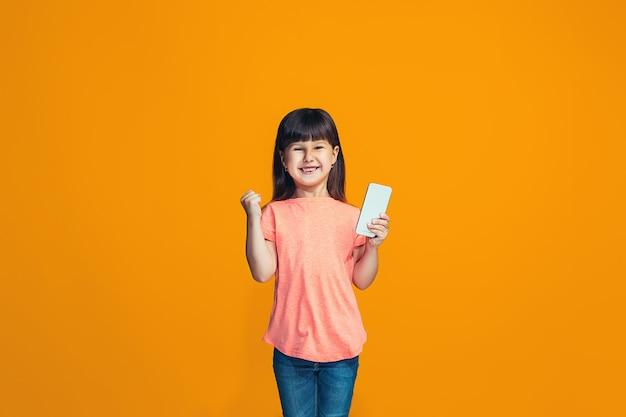 L'adolescente heureuse debout et souriant contre l'orange.