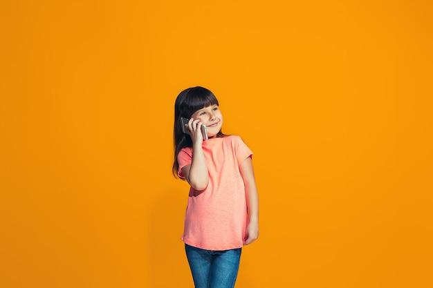 L'adolescente heureuse debout et souriant sur fond orange.