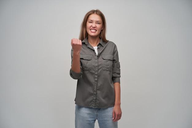 Adolescente, heureuse à la femme aux cheveux longs bruns. porter une chemise grise et un jean. notion émotionnelle. gardez le poing levé et plissez les yeux. regarder la caméra isolée sur fond gris