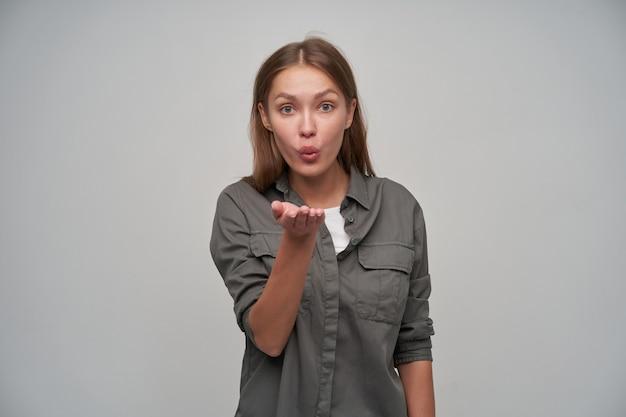 Adolescente, heureuse à la femme européenne aux cheveux longs bruns. portant une chemise grise et tenant sa main levée, vous envoyant un baiser. regarder la caméra isolée sur fond gris