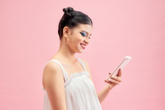 Adolescente heureuse sur le message texte de fond rose sur le téléphone portable