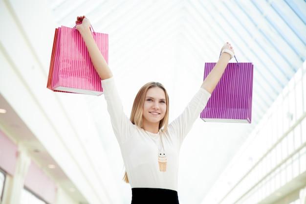 Une adolescente heureuse satisfaite de ses achats portant des sacs à provisions roses