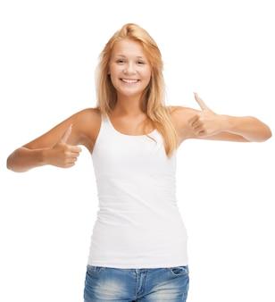Adolescente heureuse en t-shirt blanc vierge avec les pouces vers le haut