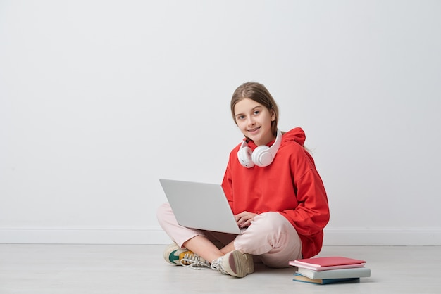 Adolescente heureuse vous regarde assis devant la caméra et étudie sur le net pendant la quarantaine à domicile en isolement