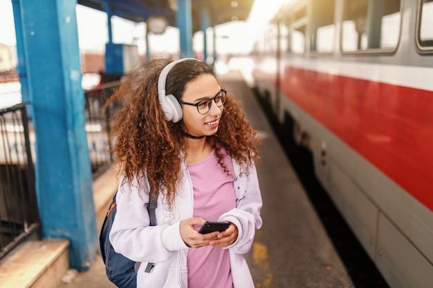 Adolescente hipster avec un casque et un téléphone intelligent à la main en attente de monter dans le train.