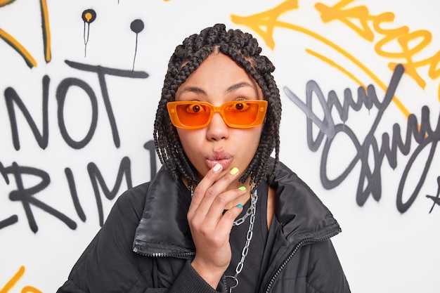 Adolescente hipster impressionnée avec des dreadlocks semble sans voix à la caméra garde la main sur les lèvres pliées porte des lunettes de soleil orange à la mode et une veste noire pose contre le mur de graffitis