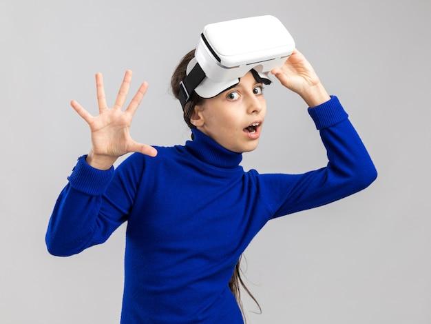 Adolescente impressionnée portant un casque vr le soulevant en regardant l'avant montrant cinq avec la main isolée sur un mur blanc