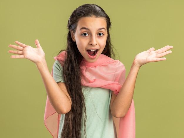 Adolescente impressionnée portant un châle regardant devant montrant des mains vides isolées sur un mur vert olive