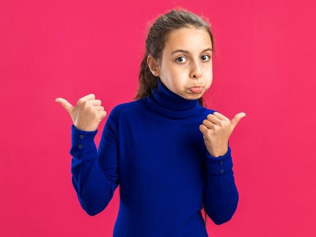 Adolescente impressionnée regardant la caméra les joues gonflées pointant sur les côtés isolés sur le mur rose