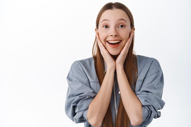 Une adolescente impressionnée regarde avec un visage fasciné, admire quelque chose de beau, regarde une chose incroyable incroyable, souriante excitée, debout sur un mur blanc