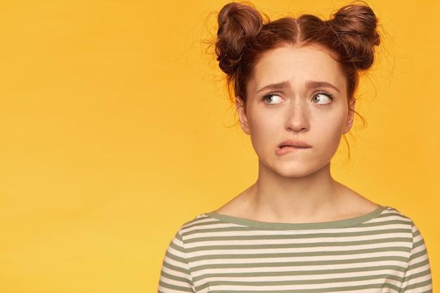 Adolescente, inquiète à la femme aux cheveux roux avec deux petits pains. mordez une lèvre dans les soucis. porter un pull rayé et regarder vers la gauche à l'espace de copie, gros plan sur mur jaune