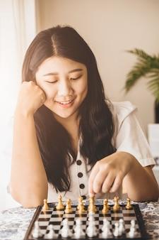 Une adolescente intelligente heureuse de jouer au jeu d'échecs à la maison pour entraîner son cerveau et sa mémoire.