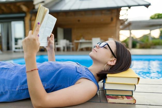Adolescente intelligente à lunettes livre de lecture, adolescent près de maison, piscine extérieure et pelouse