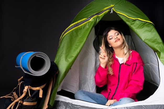 Adolescente à l'intérieur d'une tente de camping verte sur un mur noir avec les doigts se croisant et souhaitant le meilleur