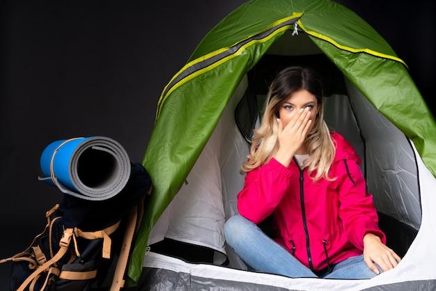 Adolescente à l'intérieur d'une tente de camping verte