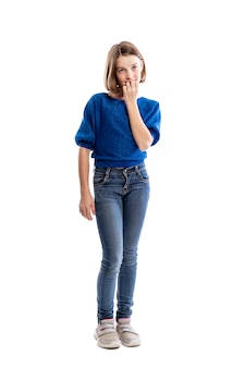 Une adolescente en jean et un sweat bleu se mord les ongles. pleine hauteur. . verticale.